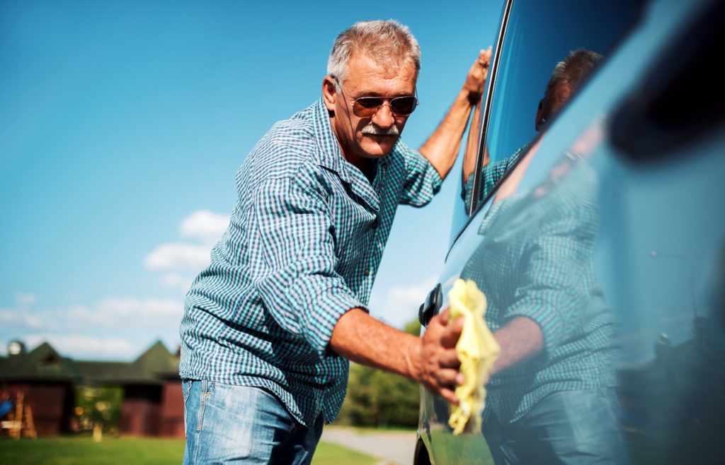 Man washing car with microfiber cloth