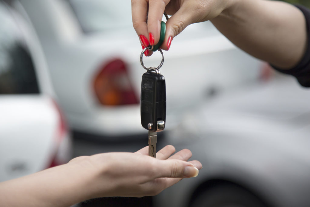 Woman receiving car key of a new car.