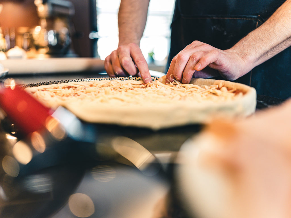 Hands of man making pizza