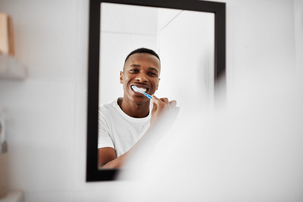 Shot of a young man brushing his teeth while looking into the bathroom mirror