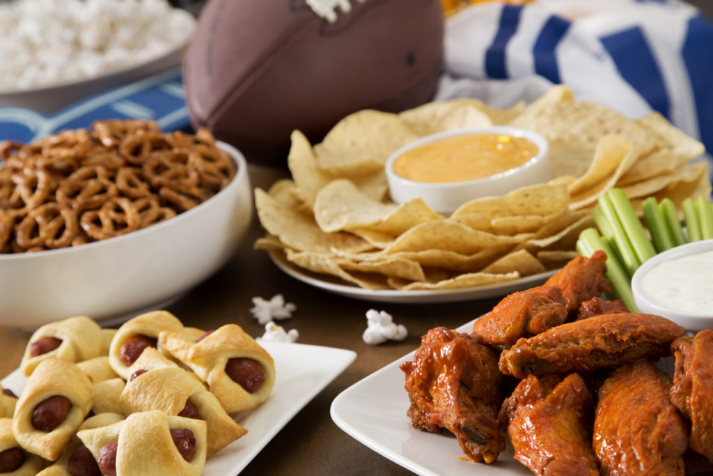 Tailgate party spread with hot wings, pig in a blanket, nachos, pretzels, and popcorn with football and a