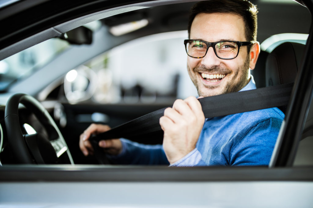 Young happy man fastening his seatbelt
